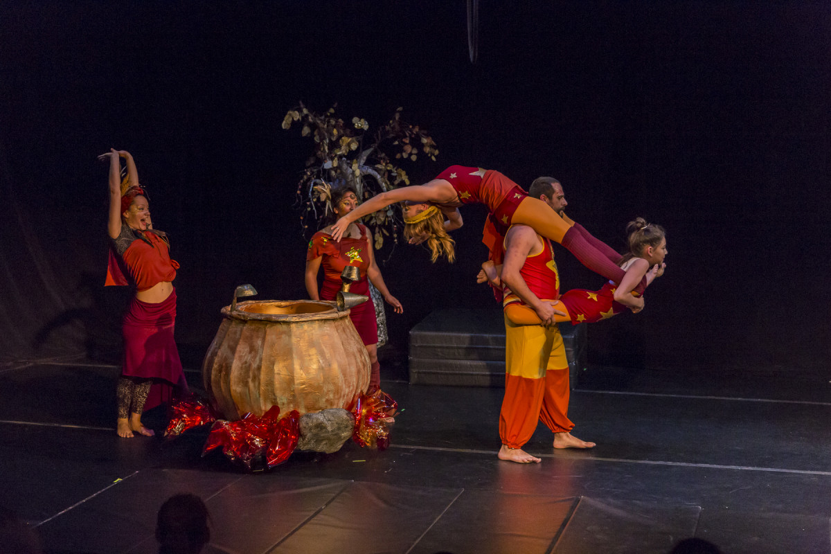 Around a pot of soup over a fire, one performer stands watching three performers in acrobatic move.